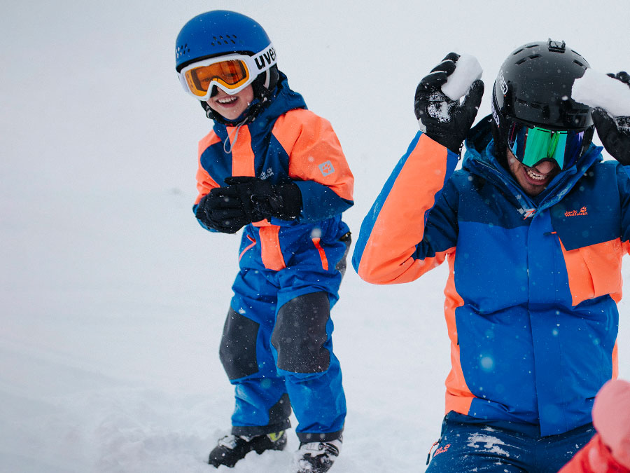 Man and child in skiwear during a snowball fight